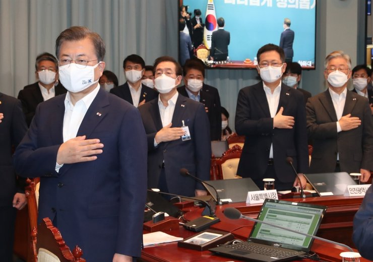 President Moon Jae-in salutes the national flag prior to a Cabinet meeting at Cheong Wa Dae, Tuesday. Gyeonggi Province Governor Lee Jae-myung, right, Incheon Mayor Park Nam-choon, second from right, and Seoul Mayor Park Won-soon, third from right, participated in the meeting to discuss measures to halt the spread of COVID-19 in the capital and surrounding area. Yonhap