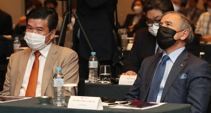 U.S. Ambassador to South Korea Harry Harris, right, and American Chamber of Commerce in Korea (AMCHAM) Chairman and CEO James Kim listen to a speech during a conference hosted by the latter at the Grand Hyatt Seoul hotel, Friday. / Yonhap