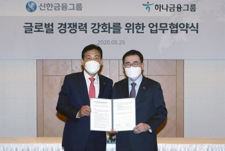 Shinhan Financial Group Chairman Cho Yong-byoung, right, and Hana Financial Group Chairman Kim Jung-tai hold a signed memorandum of understanding to form a business alliance for global expansion, at Lotte Hotel in Seoul, May 25. Courtesy of Shinhan Bank
