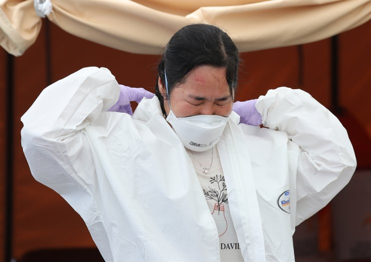 A medical staffer removes protective clothing after finishing her shift at a public health center in Seoul's Yangcheon District, Wednesday. Daytime temperature in Seoul reached over 30 degrees Celsius on that day. /Yonhap