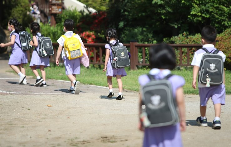 Children enter a kindergarten in Daegu, Monday, maintaining social distancing after the facility reopened following a 122-day shutdown because of the COVID-19 pandemic. /Yonhap