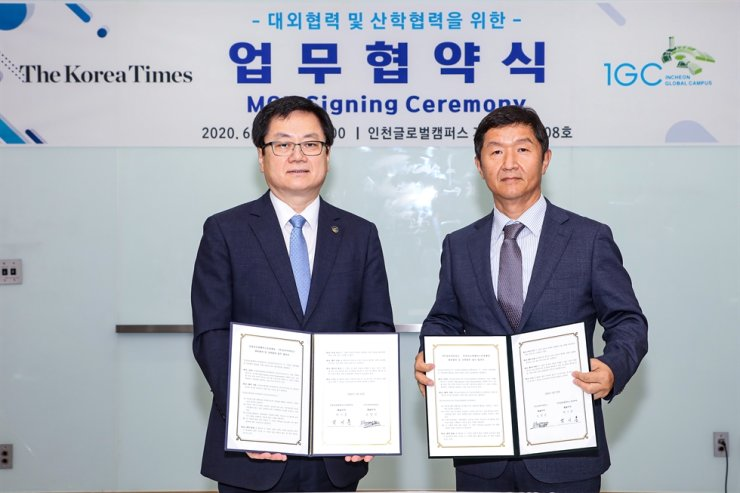 The Korea Times President and Publisher Oh Young-jin, right, and Incheon Global Campus Foundation (IGCF) CEO Paek Ki-hun pose after signing a memorandum of understanding at the IGCF multi-complex building in Incheon's Songdo, southwest of Seoul, Thursday. Korea Times photo by Choi Won-suk