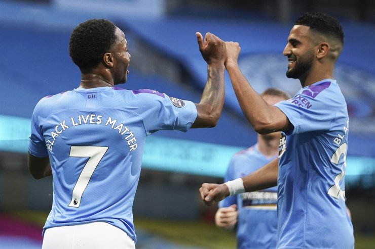 Raheem Sterling, left, of Manchester City celebrates with teammate Riyad Mahrez after scoring the 1-0 lead during the English Premier League football match between Manchester City and Arsenal FC in Manchester, Britain, Wednesday. / EPA-Yonhap