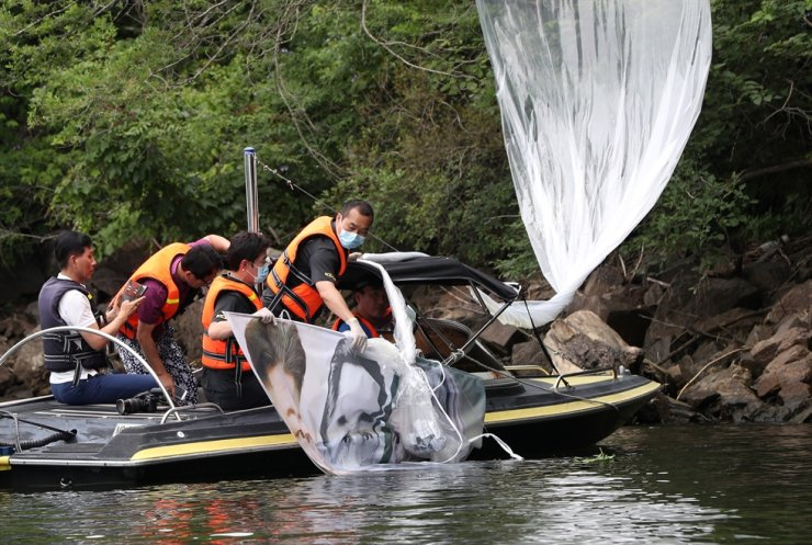 Police remove the balloon containing anti-North Korea leaflets from the water in the valley at Hongcheon in Gangwon Province, Tuesday. Yonhap