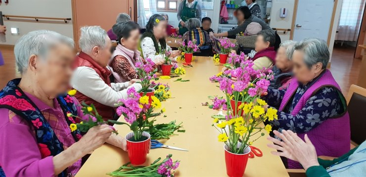 Elderly women set flowers at the Seoul geriatric care facility run by the National Health Insurance Service in Gangnam, Seoul.  Korea Times file