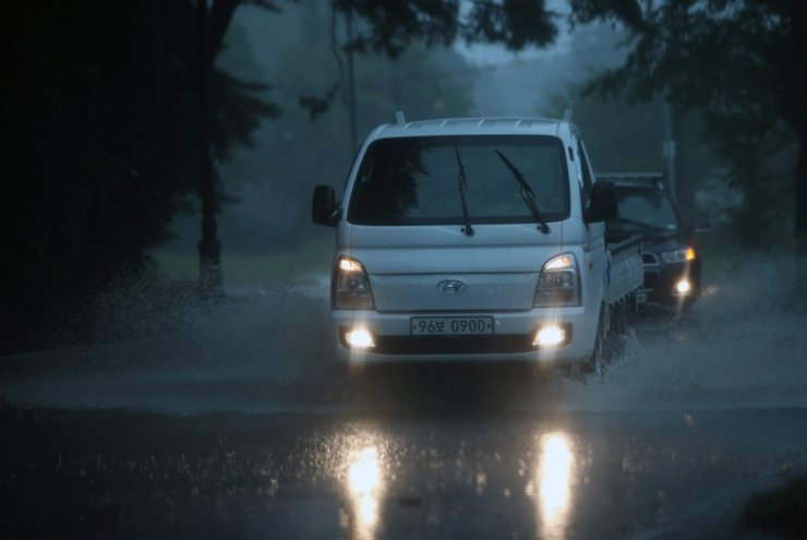 Vehicles run on a road inundated with water in Gangneung, Gangwon Province, Tuesday. Yonhap