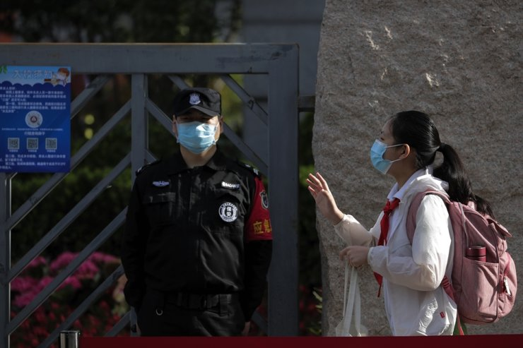 A student wearing a protective face mask to help curb the spread of the new coronavirus waves to teachers as she arrives for the reopening of a primary school in Beijing, Monday, June 1, 2020. AP