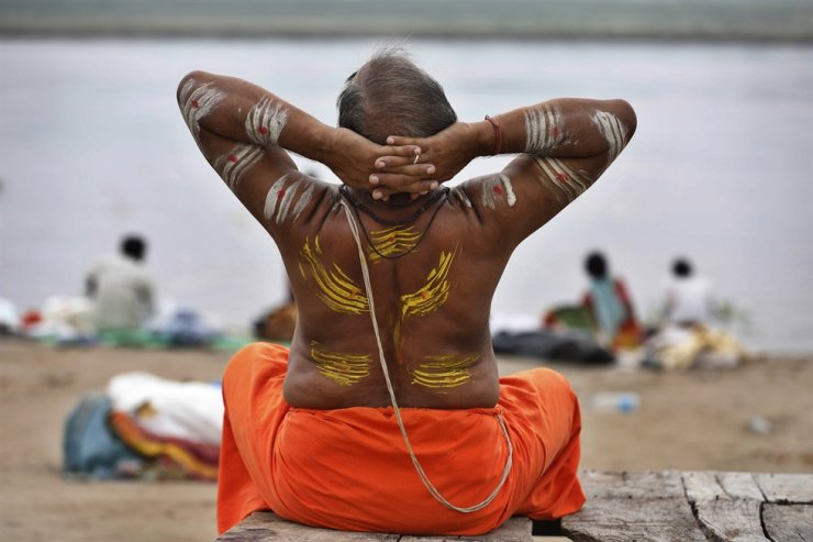 A Hindu holy man performs yoga at Sangam, the confluence of rivers the Ganges and the Yamuna in Prayagraj, India, on the International Day of Yoga, June 21. / AP-Yonhap