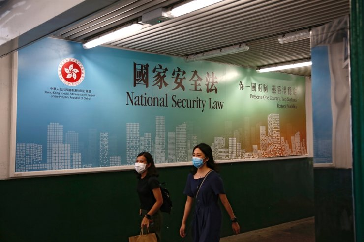Women walk past a government-sponsored advertisement promoting the new national security law as a meeting on national security legislation takes place in in Hong Kong, June 29, 2020. Reuters