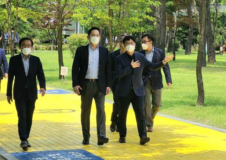 Samsung Electronics Vice Chairman Lee Jae-yong, second from left, walks with Kim Ki-nam, head of the Device Solutions Division, left, and Jung Eun-seung, right, head of the Foundry Business Division, during his visit to the company's semiconductor research center in Hwaseong, Gyeonggi Province, Friday. / Courtesy of Samsung Electronics