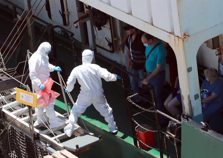 Health authorities move Russian sailors who have been confirmed to have COVID-19 to hospitals from a Russian vessel docked at Gamcheon Port in Busan, Tuesday. / Yonhap
