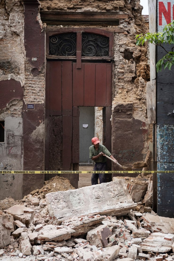 A person removes debris from a wall collapsed by a magnitude 7.4 earthquake in Oaxaca, Mexico, Tuesday. /EPA