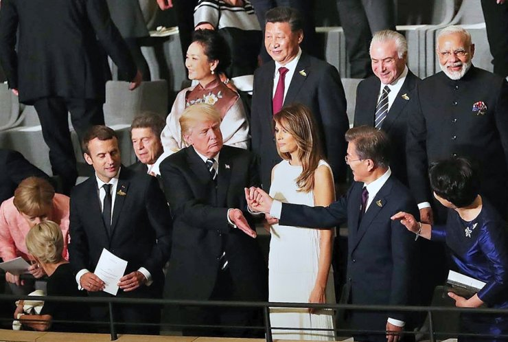 President Moon Jae-in holds hands with U.S. President Donald Trump during a G20 summit event in Germany in this July 2017 photo, with Chinese President Xi Jinping standing behind them. Korea is once again faced with diplomatic pressure over whether to side with the United States of America or the People's Republic of China. / Korea Times file