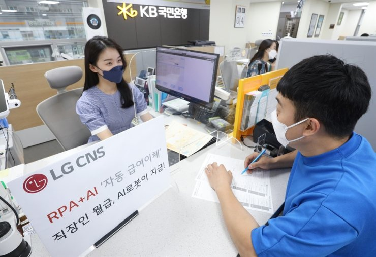 A KB Kookmin Bank employee focuses and has more time for customer consultation, as the LG CNS RPA+AI, which automatically transfers wages, reduces the burden on employees. Courtesy of LG CNS