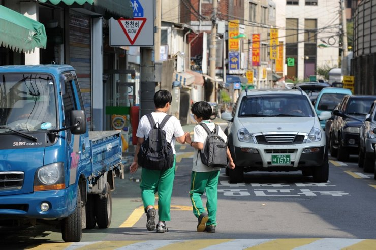 Two students walk on a road in a school zone in Seoul in this file photo. A new law delivers harsher punishment to drivers who either kill or injure children in school zones, but it has also drawn a backlash from drivers for possible discrimination against them. Korea Times file