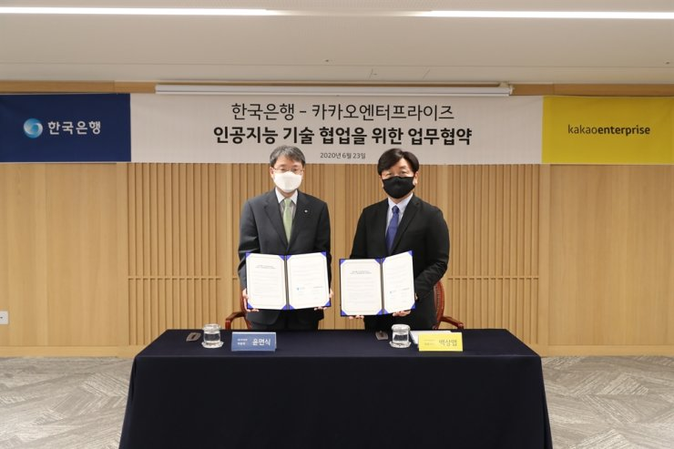 Yoon Myun-shik, left, senior deputy governor at the Bank of Korea, poses after signing a digital partnership with Kakao Enterprise CEO Baek Sang-yeop, at the headquarters of the central bank in Seoul, Tuesday. Courtesy of Bank of Korea