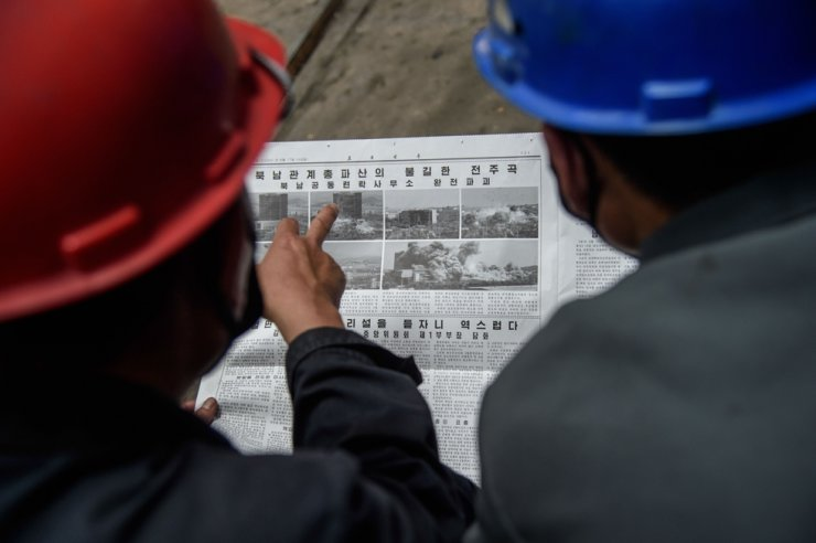 Employees of the Kim Jong Thae Electric Locomotive Complex in Pyongyang read a copy of the Rodong Sinmun newspaper showing coverage of North Korea's demolition of the north-south joint liaison office, on June 17, 2020. AFP
