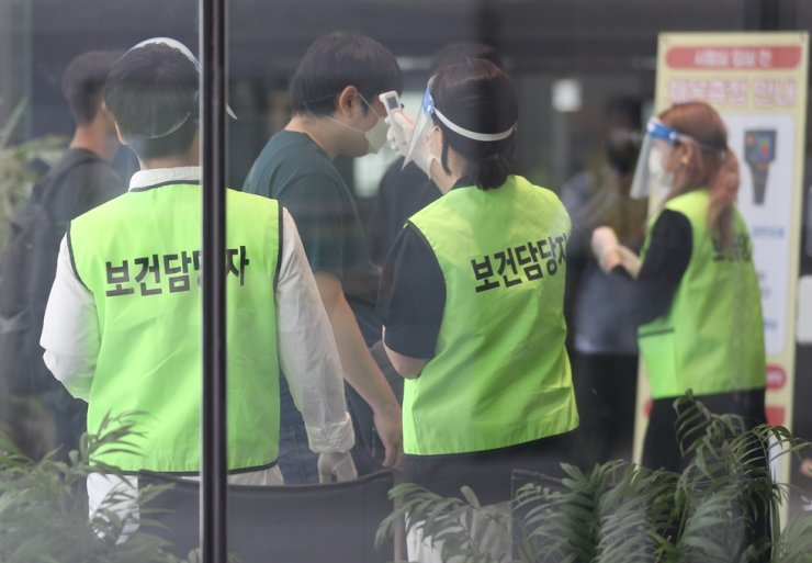 Officials take the temperature of applicants who came to take an employment exam of the Korea Railroad Corp. (KORAIL) at Myongji College in Seoul, Sunday. / Yonhap