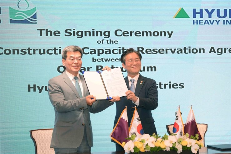 Trade Minister Sung Yun-mo, right, and Hyundai Heavy Industries President Ka Sam-hyun hold up a construction capacity reservation agreement signed between three Korean shipyards and Qatar Petroleum, at a ceremony in Seoul, Monday. / Courtesy of Ministry of Trade, Industry and Energy