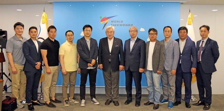 World Taekwondo President Choue Chung-won, center, with its partner firms at his office in Seoul, Friday. Courtesy of World Taekwondo