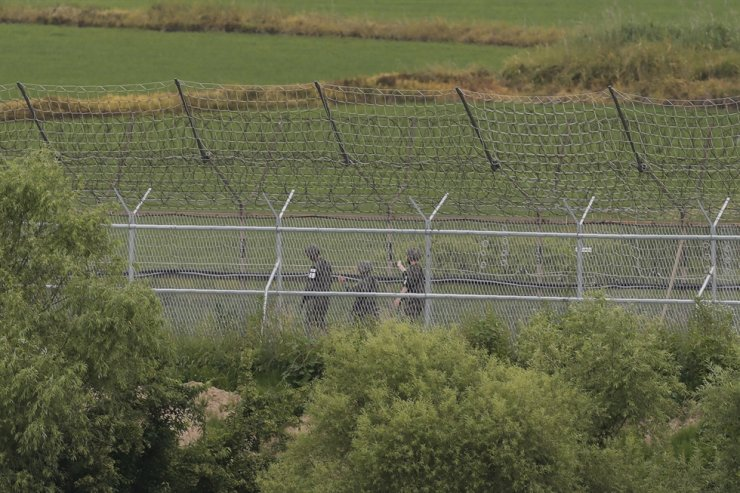 South Korean army soldiers patrol along a barbed-wire fence in Paju, South Korea, near the border with North Korea, Wednesday, June 17, 2020. AP