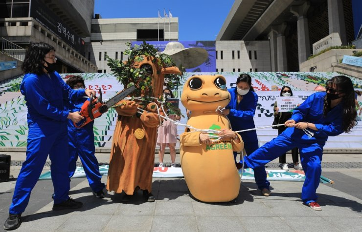 Members of the Korea Federation for Environmental Movements perform a skit in front of Sejong Center for the Performing Arts in Seoul's Jongno District, June 1, as they protest against allowing development of lands designated as urban planning sites but unprepared as city parks. News1
