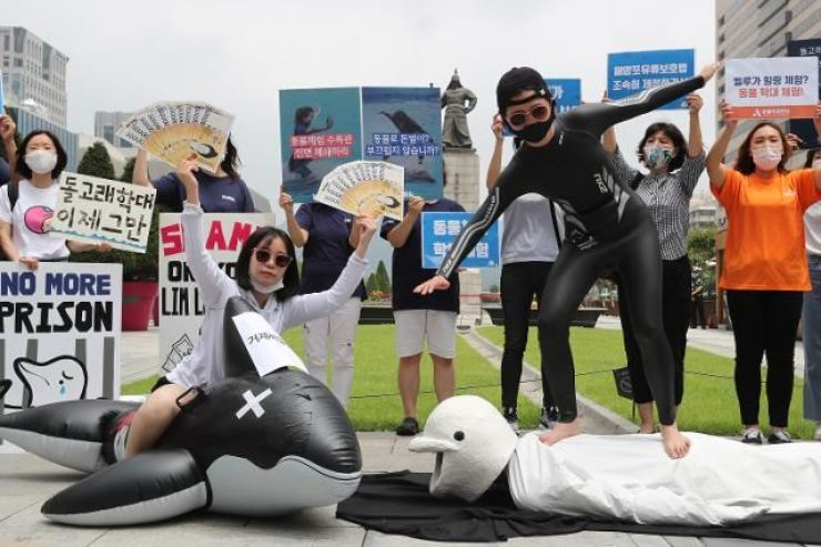 Animal and environment advocate groups at Gwanghwamun Square in Seoul's Jongno District, June 26, perform a skit to portray alleged abuse on Beluga whales and bottlenose dolphins at Geoje Sea World in South Gyeongsang Province and call for the venue's shutdown. Yonhap