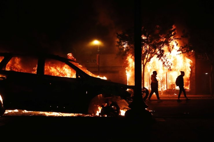 Demonstrators walk past a burning building and car during continued demonstrations in reaction to the death in Minneapolis police custody of George Floyd, in Minneapolis, Minn., U.S., May 30, 2020. Reuters