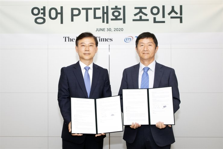 Korea Times President Oh Yong-jin, right, and ETS Korea Country Manager Paul Lee pose after signing an agreement on the English Presentation Contest at the newspaper's headquarters in Seoul, Tuesday. Korea Times photo by Choi Won-suk