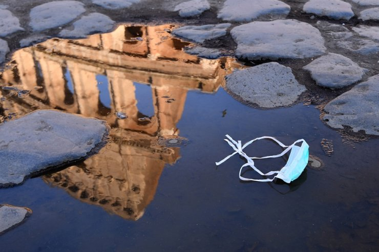 A single-use mask floats in a puddle in front of the Colosseum in Rome. AP-Yonhap
