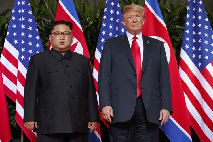 U.S. President Donald Trump poses with North Korean leader Kim Jong-un during their first summit on Sentosa Island in Singapore, June 12, 2018. AP-Yonhap