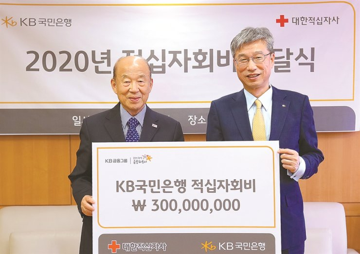 KB Kookmin Bank CEO Hur Yin, right, poses with Korea Red Cross President Park Kyung-seo after the lender donated 300 million won to the charity organization at the latter's headquarters in central Seoul, Tuesday. KB said the funds will be used to support the underprivileged hit by COVID-19. / Courtesy of KB Kookmin Bank