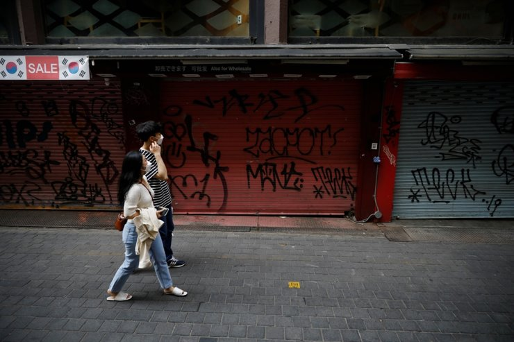 A couple wearing masks walk past closed shops amid social distancing measures to avoid the spread of the coronavirus disease (COVID-19) in Myeongdong shopping district in Seoul, May 28, 2020. Reuters