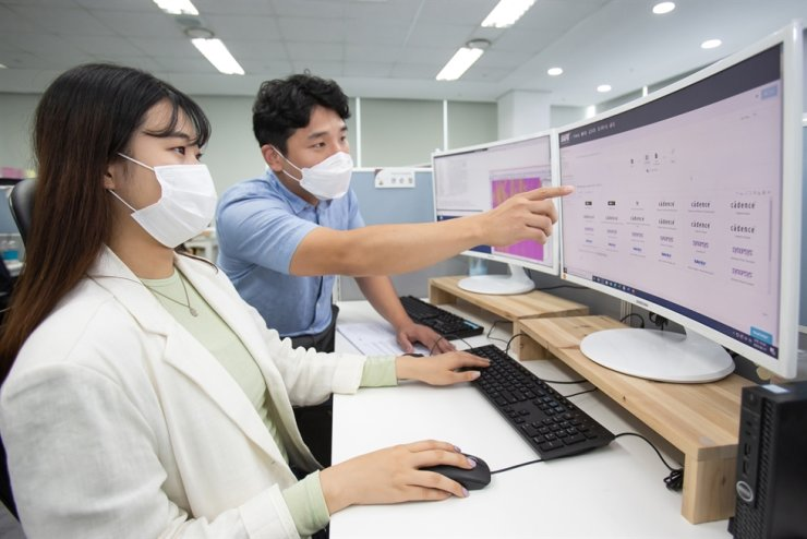 A worker at Gaonchips, Samsung's local partner, left, is involved in the chip-designing process with the help of a Samsung Electronics employee using the SAFE platform, Thursday. Courtesy of Samsung Electronics