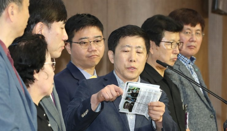 Park Sang-hak, fifth from left, head of the Fighters for Free North, a North Korean defectors' group in the South, shows propaganda leaflets the group recently sent to the North, during a press conference at the National Assembly in Seoul, June 8. Fourth from left is Rep. Ji Seong-ho, a defector-turned lawmaker with the main opposition United Future Party. Yonhap
