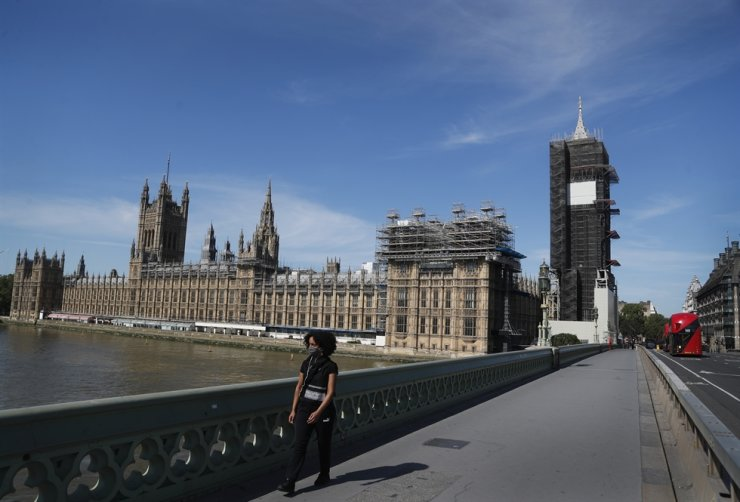 A pedestrian walks over Westminster Bridge alongside Parliament in London, Tuesday, June 2, 2020. AP