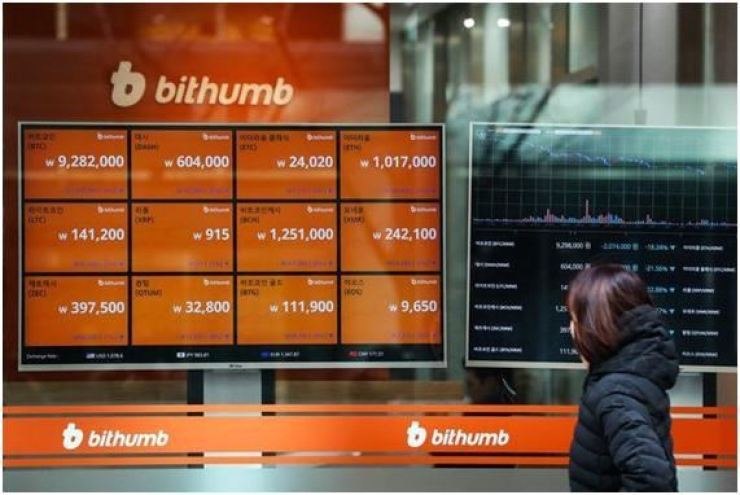 A pedestrian passes by Bithumb headquarters in Seoul in this file photo. / Korea Times file