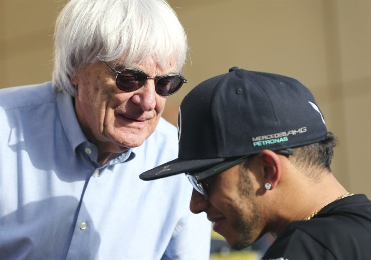 Bernie Ecclestone, President and CEO of Formula One Management, left, talks to Mercedes driver Lewis Hamilton of Britain ahead the Bahrain Formula One Grand Prix at the Formula One Bahrain International Circuit in Sakhir, Bahrain, April 16, 2015. The Formula One champion has criticized 'ignorant and uneducated' comments by the former F1 boss. Hamilton, a six-time world champion and the only Black driver in F1, was shocked by Ecclestone's claim during an interview with broadcaster CNN on Friday that 'In lots of cases, Black people are more racist' than white people. / AP-Yonhap