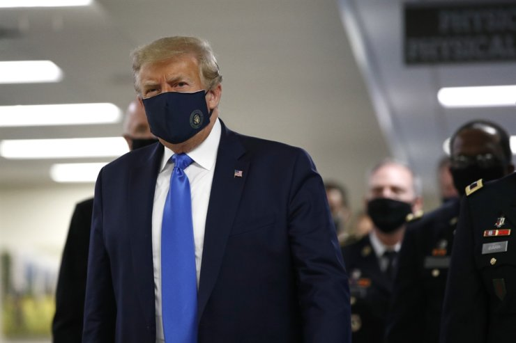 U.S. President Donald Trump wears a face mask as he walks down a hallway during a visit to Walter Reed National Military Medical Center in Bethesda, Md., Saturday, July 11, 2020. AP