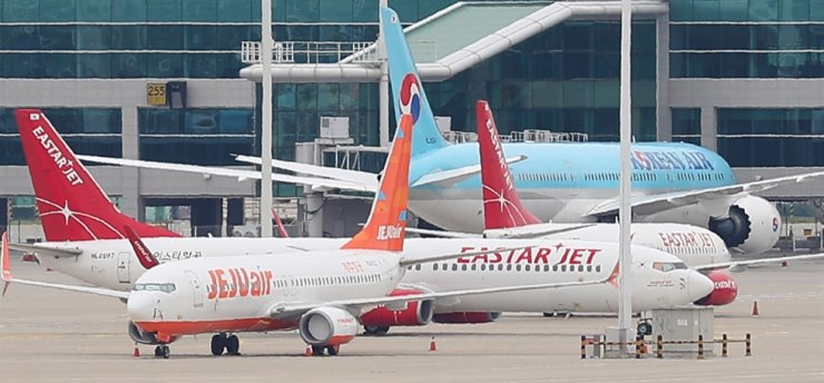 Airplanes of Jeju Air and Eastar Jet are parked at Incheon International Airport, Thursday. Yonhap