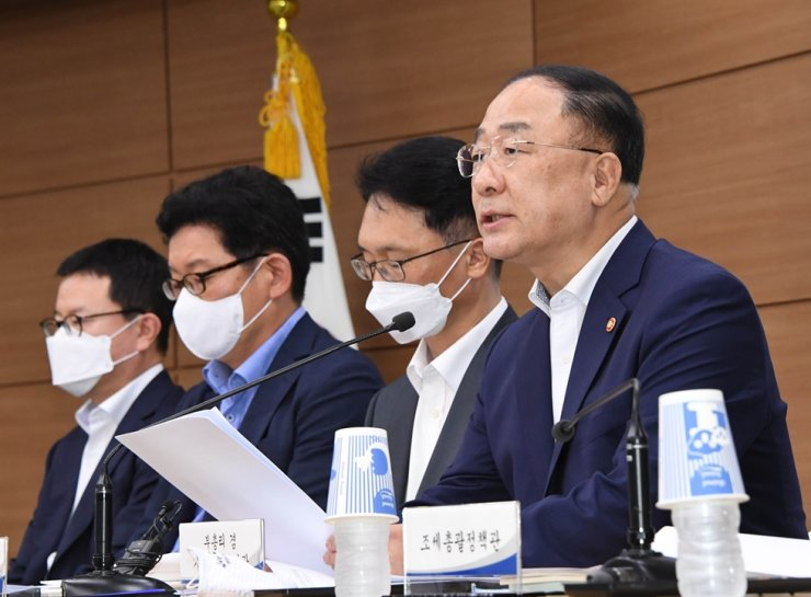 Deputy Prime Minister and Finance Minister Hong Nam-ki, right, speaks during a briefing at Sejong Government Complex, Tuesday. Courtesy of Ministry of Economy and Finance