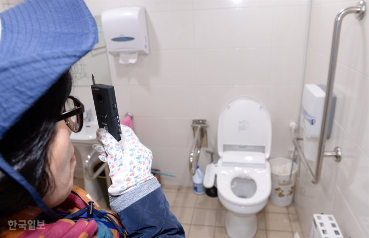 A woman checks for hidden cameras in a restroom at a community center in Yongsan, Seoul, in this March 8, 2017 photo. Korea Times photo by Hong In-ki