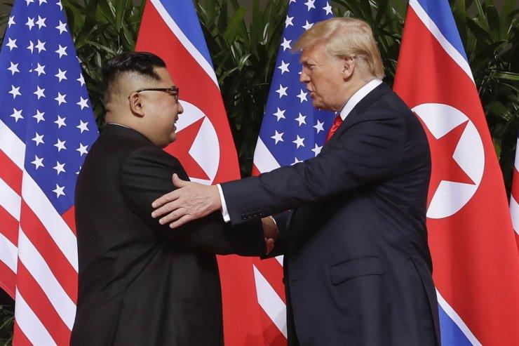 North Korean leader Kim Jong-un and U.S. President Donald Trump shake hands ahead of their summit in Singapore in this June 12, 2018, photo. / AP-Yonhap