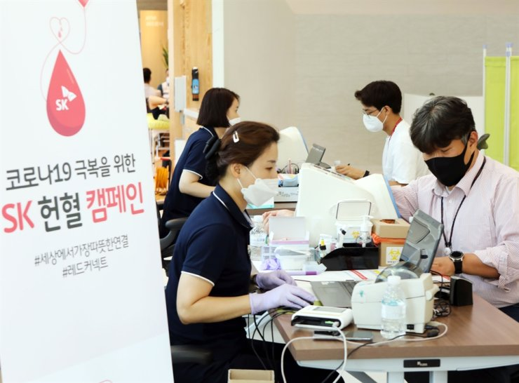 SK Group employees donate blood at their headquarters in downtown Seoul, Friday, as part of the conglomerate's blood donation campaign to address Korea's blood shortage in the wake of the COVID-19 pandemic. Courtesy of SK Group