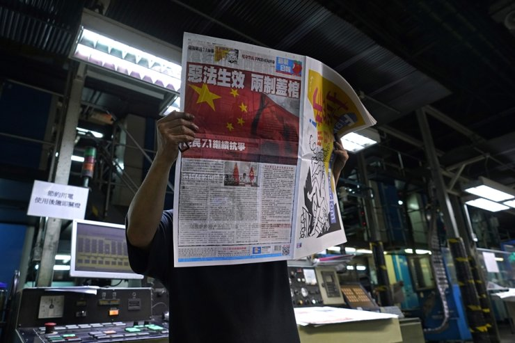 A worker checks a copy of Apple Daily's July 1, 2020, edition with the front page reading 'Draconian law is effective, one country two systems is dead' at the newspaper's printing plant in Hong Kong, Wednesday. AP-Yonhap