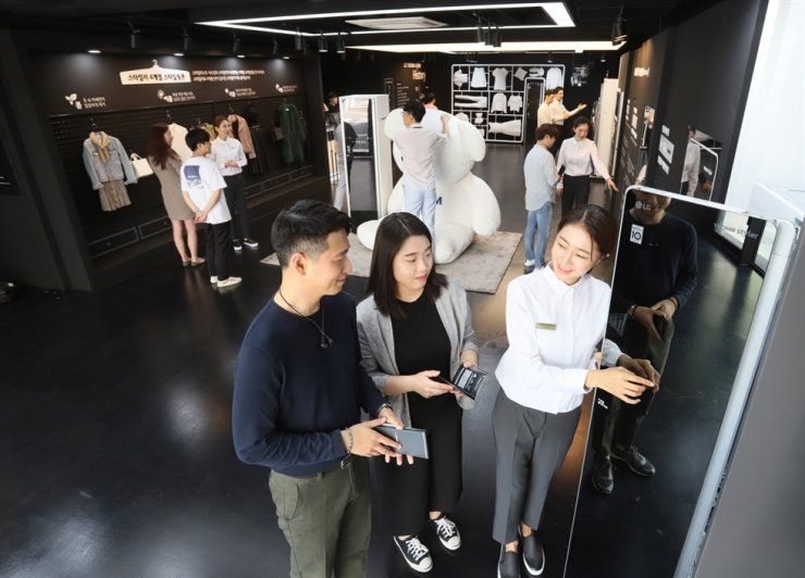 An LG Electronics employee explains the functions of the steam clothing care system 'Styler' at the tech firm's pop-up store in Sinsa-dong, Seoul, in this 2018 file photo. / Courtesy of LG Electronics