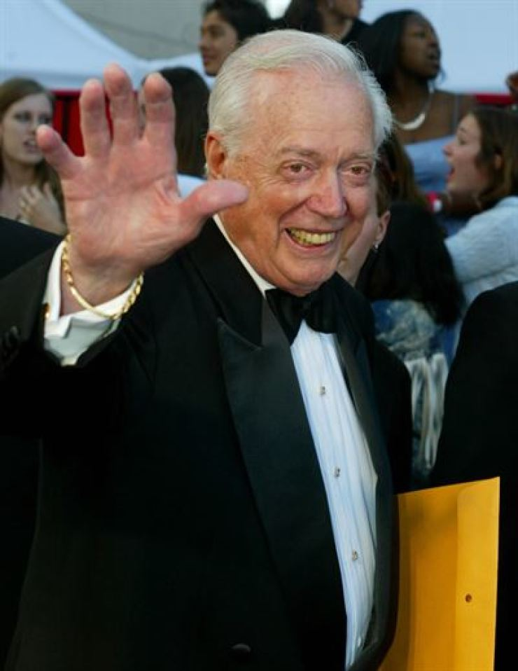 Hugh Downs, former host of the ABC news program '20/20' poses as he arrives for the ABC television networks 50th anniversary in Hollywood March 16, 2003. Reuters