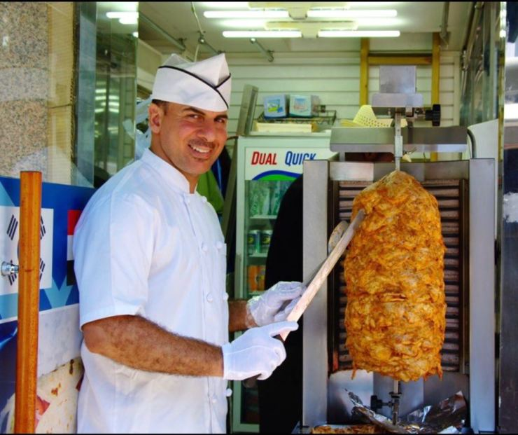 Abdulkareem Adnan slices off chicken from his vertical rotisserie at Adnan Kebab in Namdaemun Market, in this undated photo / Courtesy of Adnan Kebab
