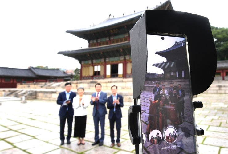 Cultural Heritage Administrator Chung Jae-suk, second from left, experiences 'Changdeok ARirang,' an augmented reality (AR) application developed by SK Telecom, at Changdeok Palace in central Seoul, Monday.