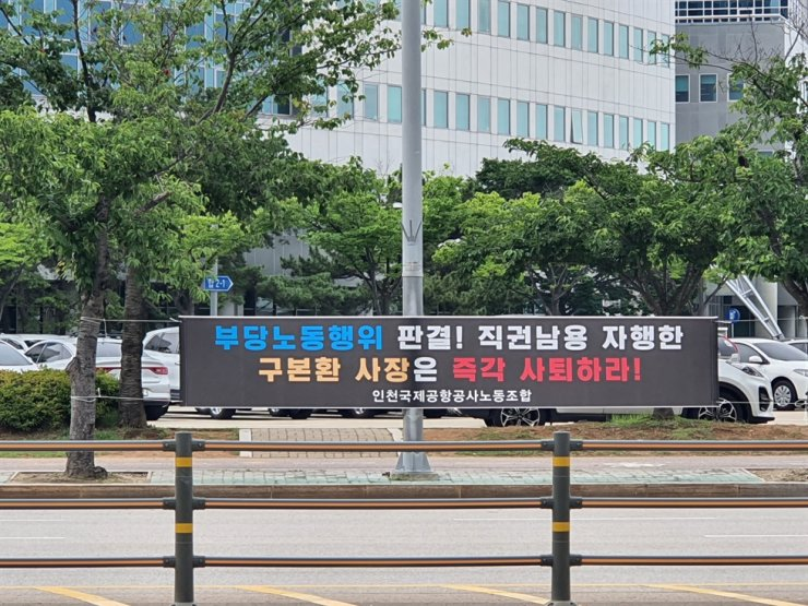 A banner hangs in the street near the office of the Incheon International Airport Corp. (IIAC), Thursday, calling on IIAC President and CEO Koo Bon-hwan to step down over the recent controversy surrounding the company's decision to directly hire subcontracted security workers. / Courtesy of union of Incheon International Airport Corp.